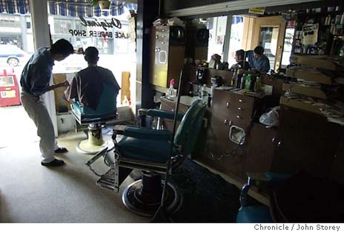 blackout_004_jrs.jpg Barber Roger Ocon cuts Volkan Aten's hair during the blackout at the Original Palace Barber Shop on Mission Street. 12/21/03 in San Francisco. John Storey / The Chronicle