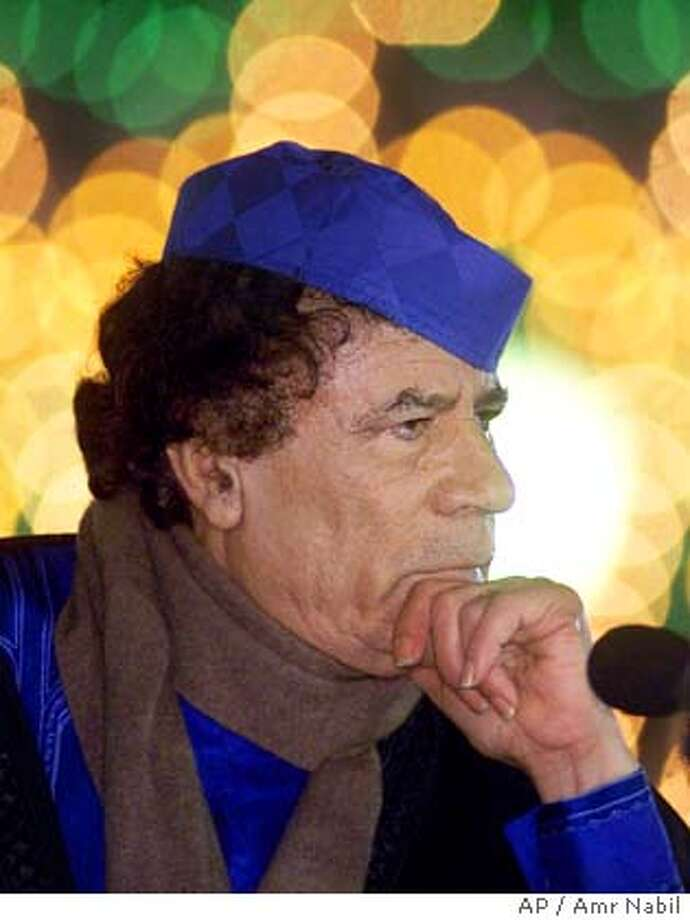 Libyan leader Moammar Gadhafi takes a question during a press conference in Triopli, Libya Monday, Feb. 5, 2001, in front of his home which was bombed by the U.S. Air Force on April 15, 1988. Gadhafi announced new evidence which he claims will prove that Libya is not involved in the 1988 Lockerbie bombing of Pan Am flight 103. A special Scpttich court in the Netherlands sentenced Abdel Basset Ali al-Megrahi to the minimum of 20 years in jail last week after finding him guilty in the attack. (AP Photo/Amr Nabil) Photo: AMR NABIL