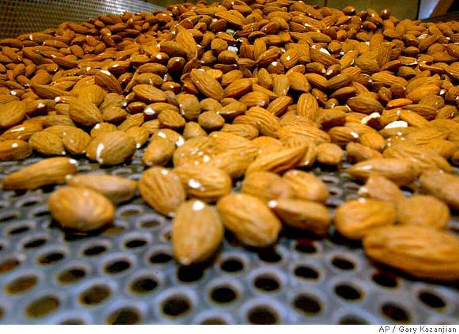 **FILE** Raw almonds are shown on a roasting tray in this file photo taken Monday, June 25, 2007 at the Sherman Thomas Ranch in Madera, Calif. The largest organization of almond growers has asked the U.S. Department of Agriculture to wait six months before enforcing a new rule requiring all California almonds to be pasteurized, saying farmers couldn't handle such a big change in time to meet the original deadline. (AP Photo/Gary Kazanjian) JUNE 25, 2007 FILE PHOTO Photo: Gary Kazanjian