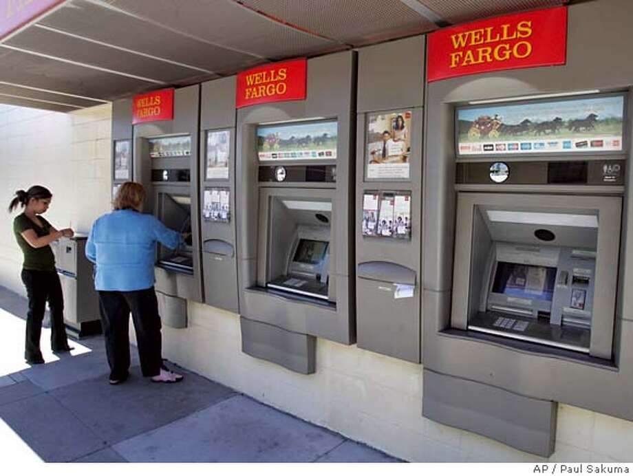 Customers use a Wells Fargo Bank ATM machine in San Francisco, Monday, Aug. 20, 2007. Service problems disabled some ATMs and online accounts at Wells Fargo & Co. for at least 24 hours starting Sunday afternoon, leaving some customers of the nation's fifth largest bank unable to get cash or use debit cards to pay for goods. (AP Photo/Paul Sakuma) Photo: Paul Sakuma