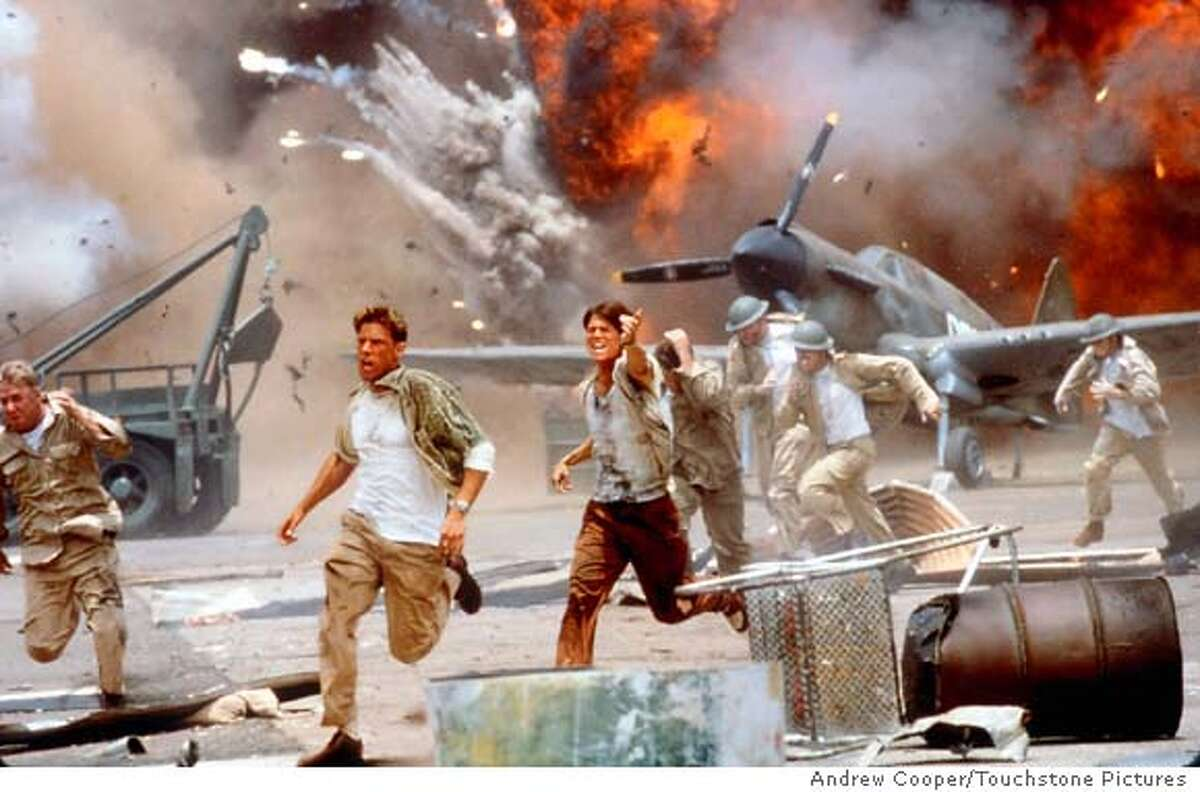 """ADVANCE FOR WEEKEND EDITIONS MAY 24-27--A scene from Touchstone Pictures new film """"Pearl Harbor"""" shows men running as the Japanese bomb an air base in this undated handout photo. WWII has provided moviemakers with plenty of material over the years in which to present the filmmaker's point of view on war. The $135 million epic """"Pearl Harbor"""" debuts on Memorial Day weekend, promising a ferocious recreation of the Japanese sneak-attack that plunged the United States into WWII. (AP Photo/Touchstone Pictures, Andrew Cooper) CAT"""