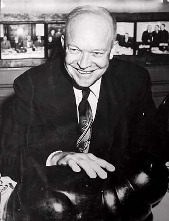 """A photograph of Dwight D. Eisenhower, with the famous black cat sculpture in front of him, hangs on a wall of the new Black Cat Bar. Sam McCullagh and his wife Cindy Testa-McCullagh (cq) are members of the University Club on Nob Hill and creators of the Black Cat Bar in the club at 800 Powell Street. A scarred and weathered Benny Bufano sculpture of a black cat named """"Tombstone"""" graces the bar top and joins other memorabilia from the old San Francisco Press Club. Email: mcculla@aol.com  Chris Stewart / The Chronicle  Sam McCullagh; Cindy Testa-McCullagh MANDATORY CREDIT FOR PHOTOG AND SF CHRONICLE/NO SALES-MAGS OUT Photo: Chris Stewart"""