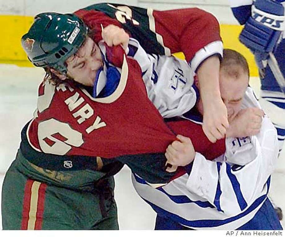 Minnesota Wild defenseman Alex Henry, left, takes a swing at Toronto Maple Leafs right wing Tie Domi, right, as Domi tries to pull Henry's jersey over his head during a second-period fight in St. Paul, Minn., Thursday, Dec. 11, 2003. Both players received major penalties for fighting. The Maple Leafs won 1-0. (AP Photo/Ann Heisenfelt) Photo: ANN HEISENFELT