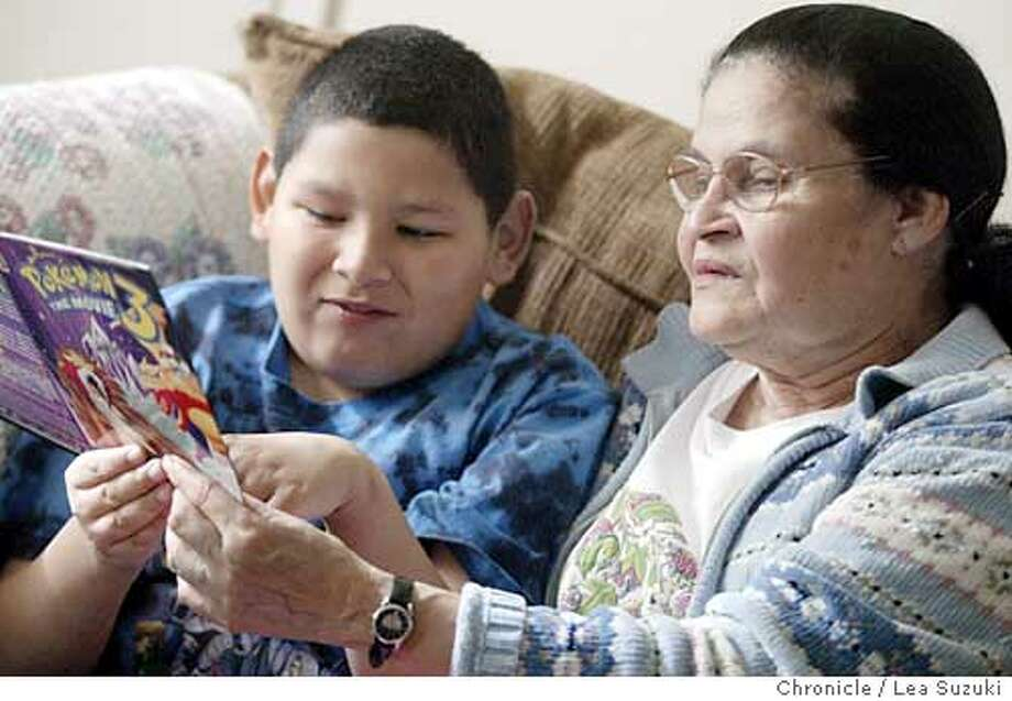 Season of Sharing story. From left: Juanita LaMania and Christian, her grandson, try to decipher some symbols on a Pokemon DVD box on 11/26/03, in Sunnyvale, CA. Juanita LaMania is 66 and has raised five grandchildren. After living in same house for 25 years, owner decided to sell it and she had to move. She is retired and still has youngest grandchild, Christian Martinez, who is 9, living with her. SOS helped with security deposit for her new apartment. Without the help, she couldn't afford to move. Photo by LEA SUZUKI / The San Francisco Chronicle Photo: LEA SUZUKI