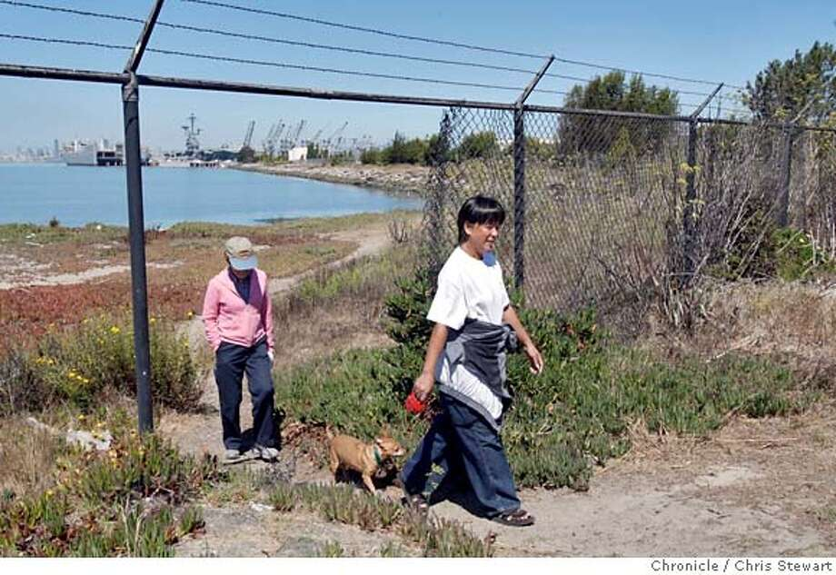 TRAIL20_0005_cs.jpg Event on 8/17/07 in Alameda  Ella Pennington (cq - right), of San Leandro, leads her dog Cuervo and Linda Berggren (cq), of Alameda, following a hike along what will be a new trail opening to the public at Alameda Point, site of the former Alameda Naval Air Station. It will open up the formerly off-limits shoreline to the public between the Encinal Boat Ramp and the aircraft carrier USS Hornet. The 2600 foot shoreline will feature a new paved trail, benches and the removal of a 635-foot-long chain link fence that blocked access to the shore. Photographed August 17, 2007. Chris Stewart / The Chronicle Trail20, Ella Pennington, Linda Berggren MANDATORY CREDIT FOR PHOTOG AND SF CHRONICLE/NO SALES-MAGS OUT Photo: Chris Stewart