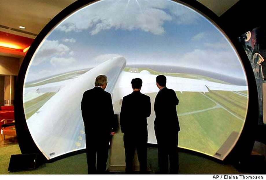 ** ADVANCE FOR WEEKEND EDITIONS OF DEC. 6-7 ** Boeing employees watch a three-dimensional, animated video of the proposed Boeing 7E7 jet, at a meeting for airline representatives Thursday, Nov. 13, 2003, in Seattle. Boeing Co. has hosted a contest to nickname its proposed 7E7 airplane, spurred a nationwide bidding war among communities wanting to build the jet and recently announced work assignments for its worldwide partners in the project. (AP Photo/Elaine Thompson) Boeing employees watch a three-dimensional, animated video of the proposed 7E7 jet, designed to return romance to flight. Photo: ELAINE THOMPSON