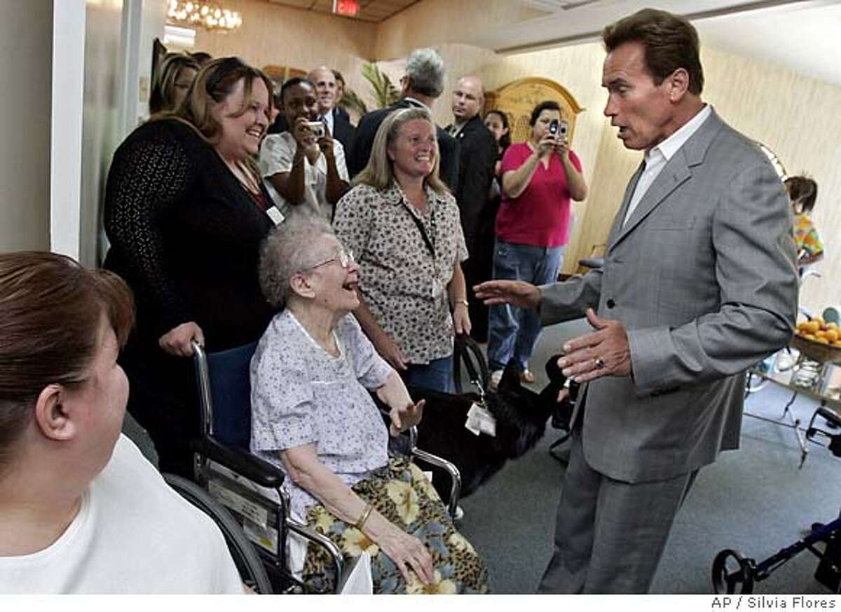 California Gov. Arnold Schwarzenegger talks with resident council president Lillian Sherman, in wheelchair, and activities assistant Julie Savage, second from left, as he tours the Community Care and Rehabilitation Center in Riverside, Calif., Wednesday, Aug. 15, 2007. His visit drew attention to the state budget impasse and how it is affecting the care center. (AP Photo/Silvia Flores, Pool) POOL PHOTO