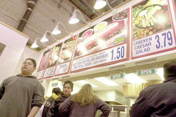 bigbox07_112903_kocihernandez  Customers stop by the foodcourt, after shopping.Food court at Costco, in SF. This season, thousands of people will find themselves stuck in a big store with long lines and empty stomachs. Good thing there's a proliferation of burgers, pizza, even meatballs offered at your local mammoth retailer.  CHRISTINA KOCI HERNANDEZ / The Chronicle Jomyr Bautista of San Leandro grabs the family's shopping cart on which dangles a new suit he is getting for Christmas. Jomyr Bautista of San Leandro grabs the family's shopping cart on which dangles a new suit he is getting for Christmas.