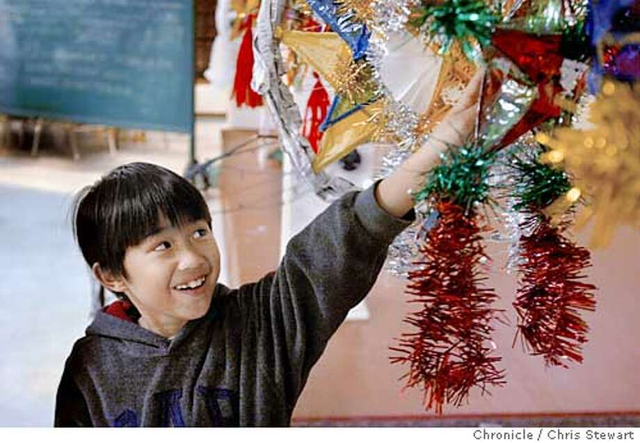 Event on 12/6/03 in San Francisco. Steuart Arboleda (cq), 10, proudly reaches for his completed parol (Filipino Christmas lanterns made of bamboo sticks and colorful plastic or paper). As part of their Christmas celebration, the Filipino American Development Foundation holds a parol-making workshop at St. Patrick's Church, Social Hall, 756 Mission Street, SF. The organization will have a parade of parols from 6th Street to St. Patrick's Church on Dec. 15. Chris Stewart / The Chronicle MANDATORY CREDIT FOR PHOTOG AND SF CHRONICLE/ -MAGS OUT Photo: Chris Stewart