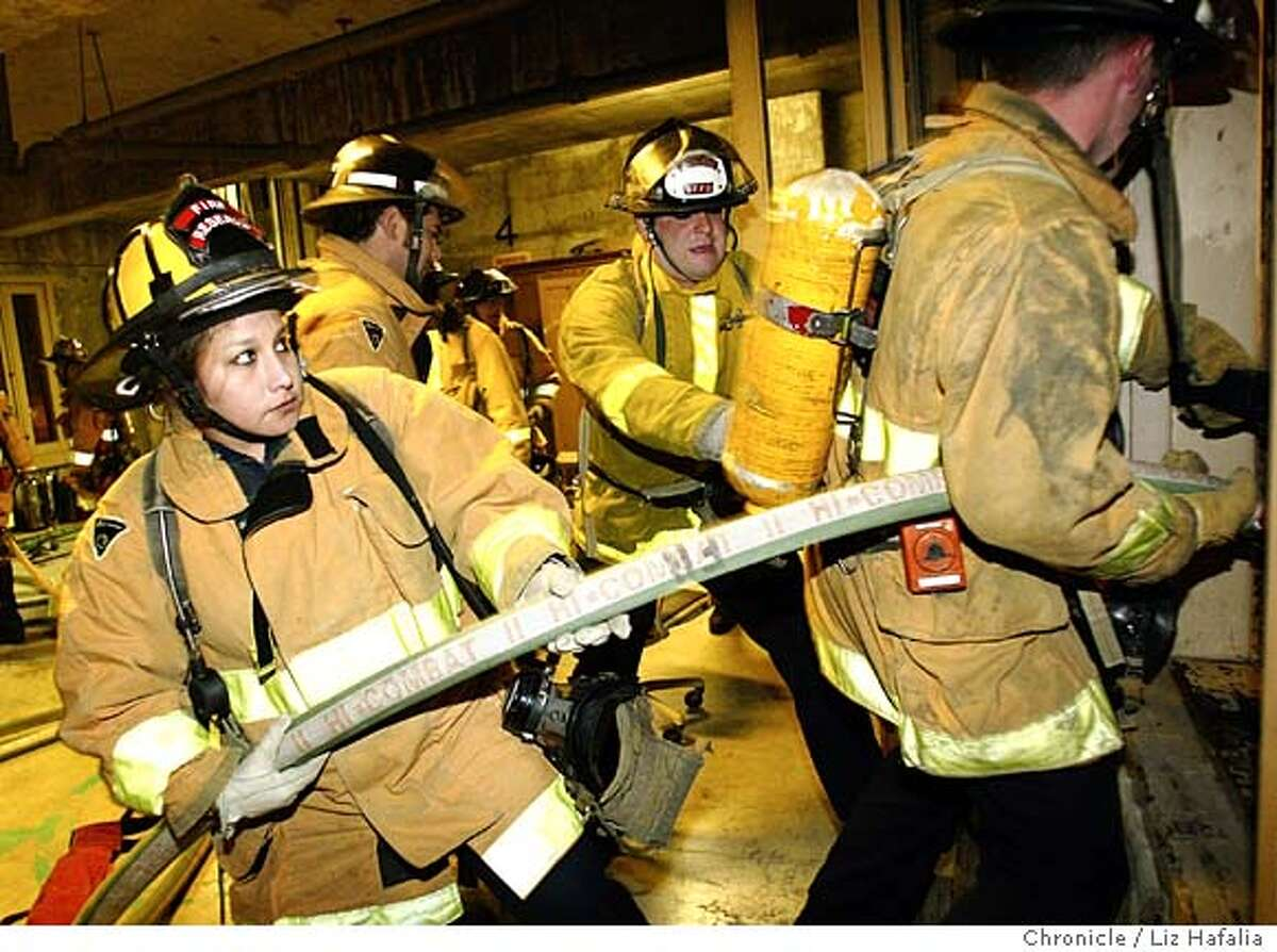 San Francisco Fire Department's Reserve Academy trains reserve firefighters who accompany S.F. Fire Dept. members on emergency runs and fires. Gabriel Salvador (left) has been in the reserve for 4 years. Shot on 11/20/03 in San Francisco. LIZ HAFALIA / The Chronicle
