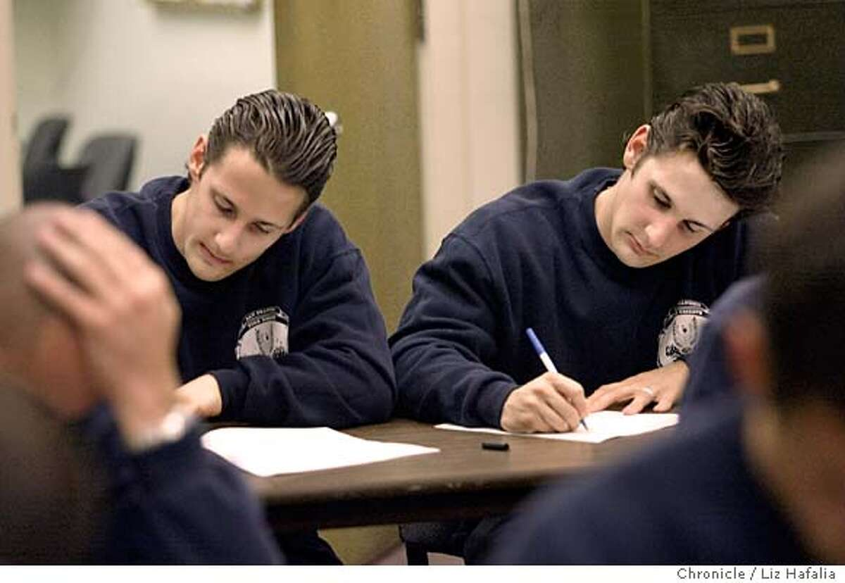 San Francisco Fire Department's Reserve Academy trains reserve firefighters who accompany S.F. Fire Dept. members on emergency runs and fires. Nicholas Restani (left) and his brother Dominic Restani (right), are both 24 years old, and are taking a reserve training exam. Shot on 11/20/03 in San Francisco. LIZ HAFALIA / The Chronicle