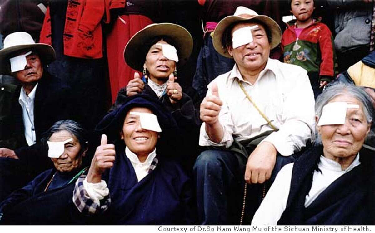 """The Tibetans with their thumbs up have just been operated on by Seva ophthalmic surgeons in Tibet; the Chinese text says: """"We thank the American Seva Organization for giving back sight to so many of our blind people"""". photo by Dr.So Nam Wang Mu of the Sichuan Ministry of Health."""