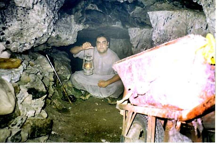 AFGHAN10.jpg  A Contra Costa Afgani boy Hyder Akbar 18, in a cave in eastern Afghanistan.Travels back to parents home and documents his trip on tape for NPR.