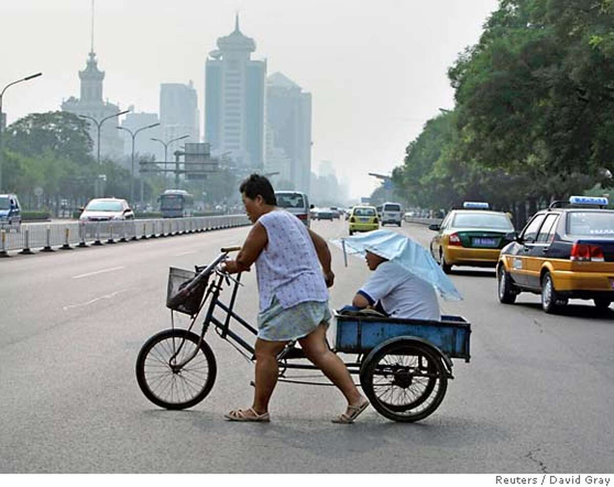 A man pushes a bicycle as another sits on it while holding an umbrella along a main road in Bejing August 17, 2007. Beijing embarked on a four-day experiment on Friday to see if taking 1.3 million cars off the city's streets will substantially reduce air pollution at next year's Beijing Olympics. The plan involves drivers with an even final digit on their licence plate facing fines if they take to the city roads today and Sunday, while odd numbered cars are banned Saturday and Monday. REUTERS/David Gray (CHINA) 0