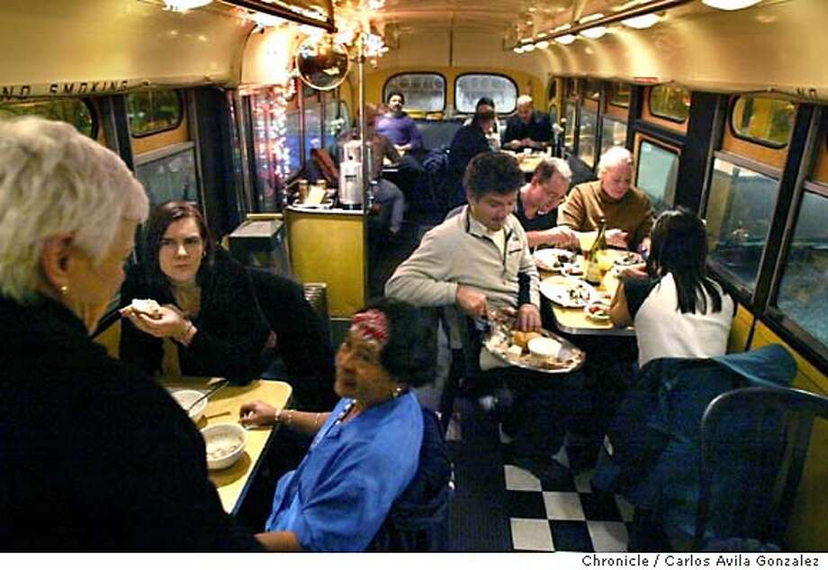 Patrons enjoy their meals prepared by Joe, the chef and maitre'd of this exclusive, secret restaurant inside an old school bus. It's parked, and never moves, and Joe has renovated it with a kitchen and 15 tables. The New York native has been serving home food to his friends and their friends for the past six years, only on Monday nights, at dark, during winter. It's hush hush because he has no permits to operate a restaurant. But some of the bay area's best foodies and eaterrati know about Joe's little gem. But you have to know someone who knows someone to get in. (Note: please do not include the city in the caption as the location of the bus needs to remain secret)  Photo by Carlos Avila Gonzalez/The San Francisco Chronicle  Photo taken on 12/01/03, in Oakland, Ca. Photo: Carlos Avila Gonzalez