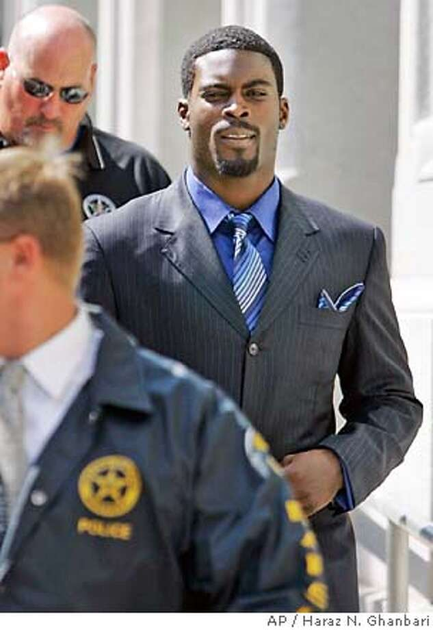 ** FILE ** Escorted by U.S. Marshals, Atlanta Falcons quarterback Michael Vick, right, leaves the federal courthouse in Richmond, Va., following his arraignment, in this July 26, 2007 file photo. (AP Photo/Haraz N. Ghanbari, Pool) POOL PHOTO MADE JULY 26, 2007. Photo: Haraz N. Ghanbari