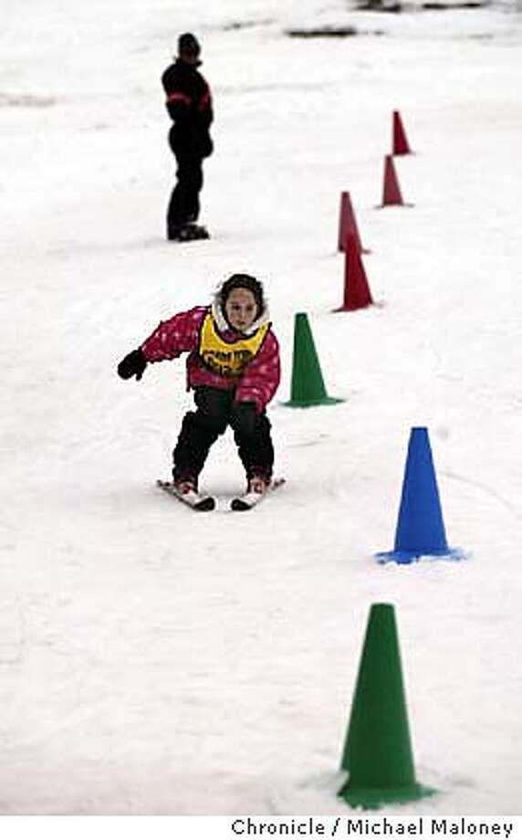 Six year old Montana Miller of El Dorado Hills snowplows her way between cones as ski instructor Jill Dehner looks on. Part of a ski school called Snow Kids held at Squaw Valley Ski Resort for kids 4-12 years old.  Photos of winter/snow activities for the Outdoors Quarterly.  Event on 11/30/03 in Sierras.  MICHAEL MALONEY / The Chronicle Photo: MICHAEL MALONEY