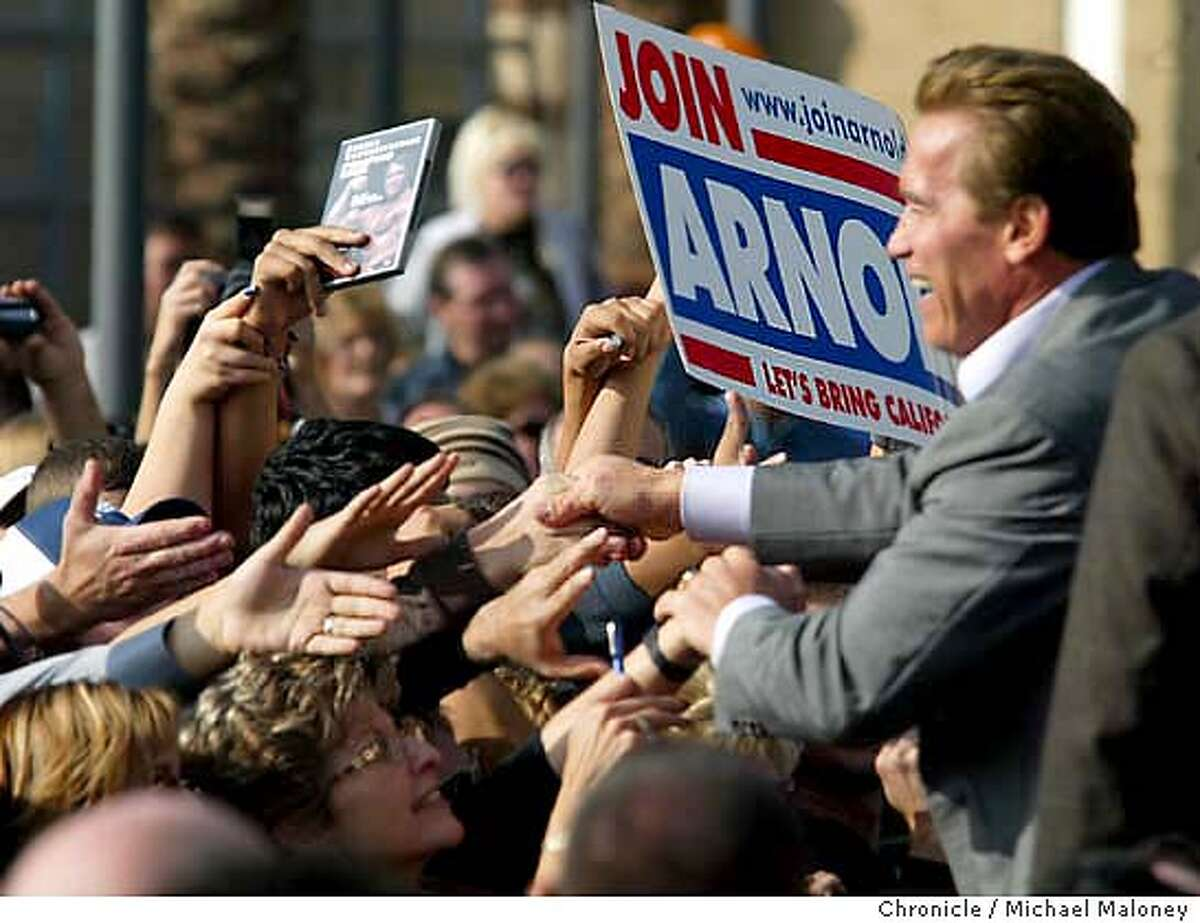 Governor Arnold Schwarzenegger shakes hands with the crowd after his speech. A Pumping Iron DVD and an old campaign sign are held out for his autograph. Governor Arnold Schwarzenegger speaks in Bakersfield at an outdoor rally asking support for his California Recovery Plan. The rally was held at the Valley Plaza Mall. MICHAEL MALONEY / The Chronicle