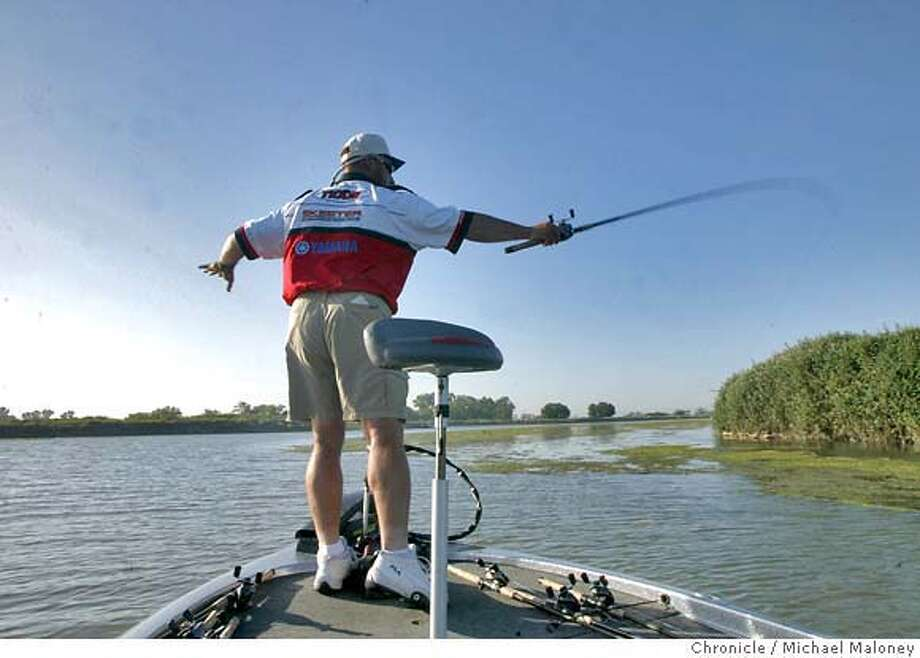 BASSFISHING018_MJM.jpg  At the bow of his bass boat, Barrack pitches his lure towards a moss bed. At his feet are other rods already strung with various lures, ready for action.  Fishing for black bass in the delta with professional bass fisherman/guide Bobby Barrack of Oakdale.  Event on 5/22/03 in OAKLEY. MICHAEL MALONEY / The Chronicle MANDATORY CREDIT FOR PHOTOG AND SF CHRONICLE/NO SALES-MAGS OUT Photo: MICHAEL MALONEY