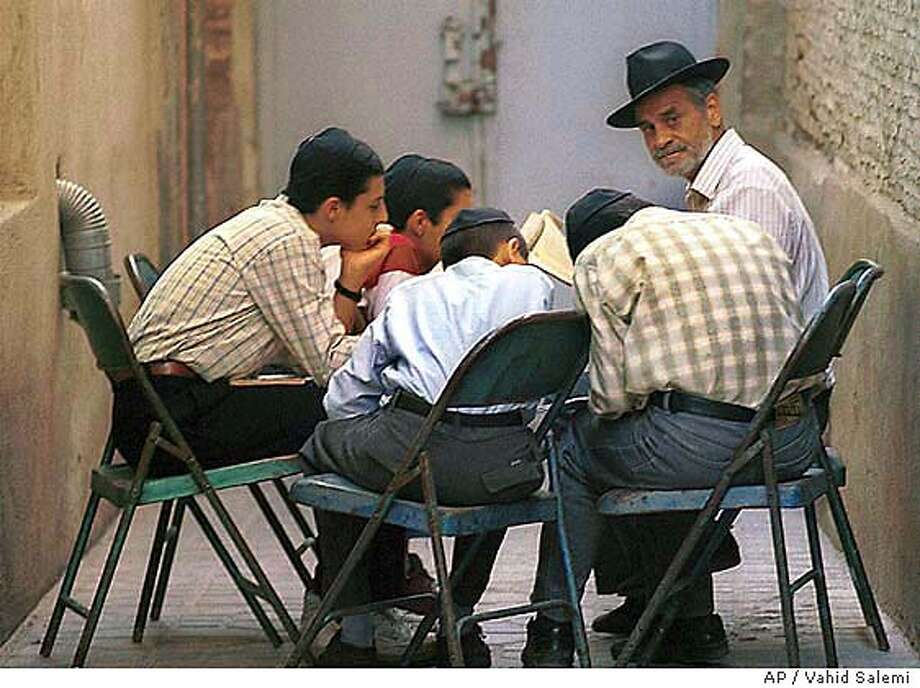 Iranian Jewish religious teacher Manouchehr Natanyakhma, right with hat, tutors Jewish students at the Rabeezadeh Synagogue in Shiraz, southern Iran Tuesday, May 9, 2000. In the wake of two Iranian Jews' televised confessions to spying for Israel, the Jewish minority that has lived in Iran for more than 2,000 years is retreating into isolation, fearing their countrymen will brand them traitors. The two defendants are from a group of 13 Iranian Jews on trial for espionage before a closed revolutionary court (AP Photo/Vahid Salemi) Photo: VAHID SALEMI