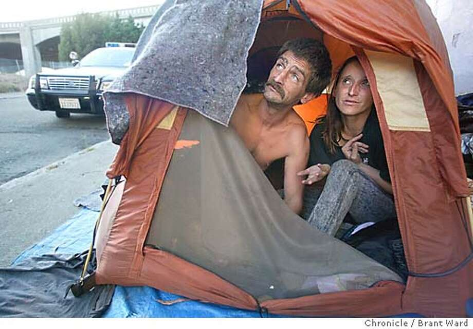 Anthony Cook and his wife Michelle plead with a San Francisco policeman who has stopped and told them to move their tent...a business in the area has complained about their presence. They are living underneath the Bay Bridge on Rincon Hill. BRANT WARD / The Chronicle Photo: BRANT WARD