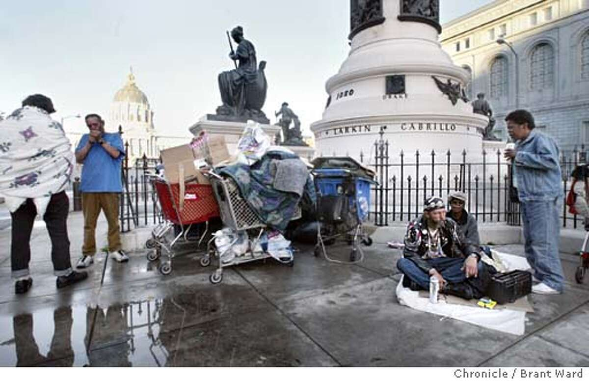 A group of homeless people gather under the City Hall statuary one morning...they are not allowed to sleep here but gather in the morning to talk and listen to music. BRANT WARD / The Chronicle