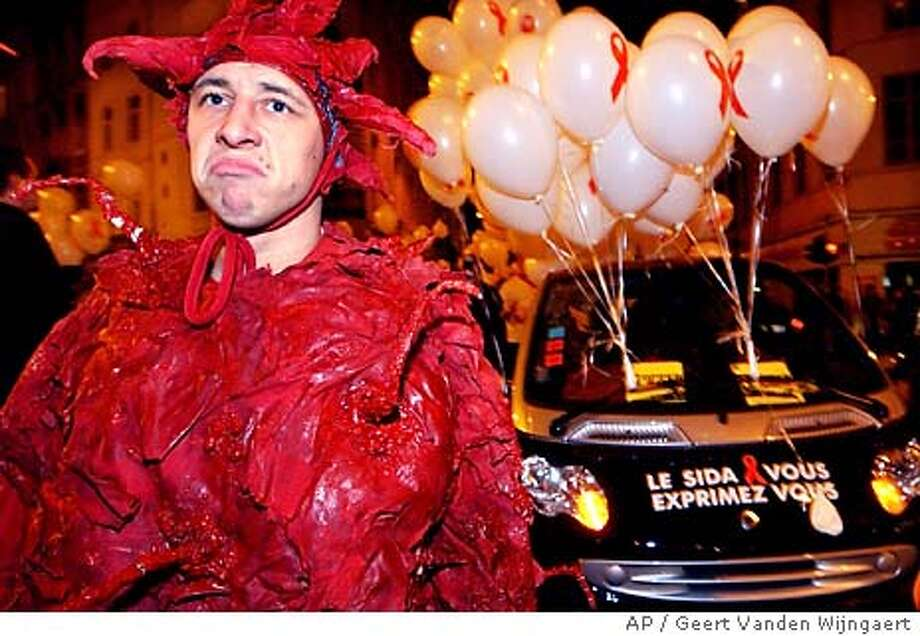 """A man dressed as an HIV virus participates in the World AIDS Day march in Brussels, Monday, Dec. 1, 2003. The slogan on the car at right reads in French """"You and AIDS, express yourself"""" (AP Photo/Geert Vanden Wijngaert) Photo: GEERT VANDEN WIJNGAERT"""