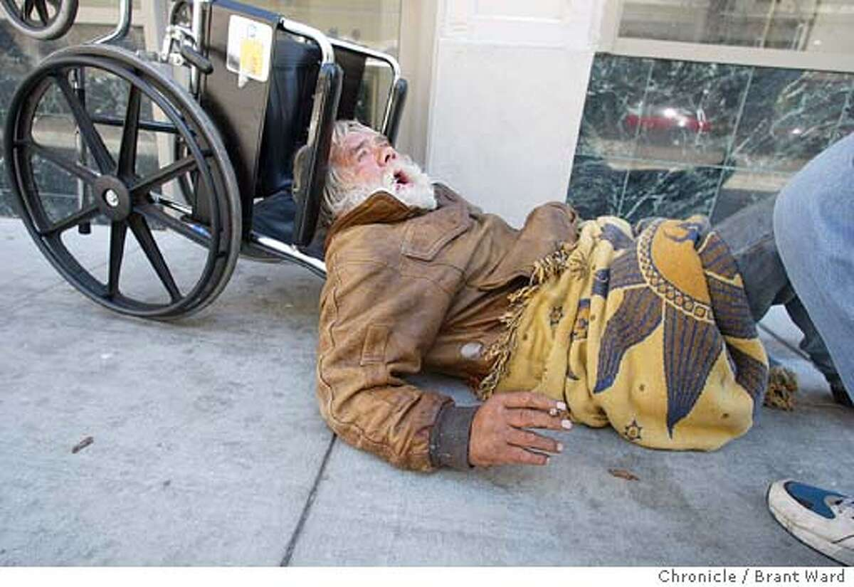Mark Russell, who is in his 60s, has been homeless for years. Here he falls out of his wheelchair on Eddy Street and then pleads for help...no one stops to help. BRANT WARD / The Chronicle