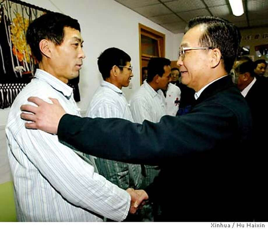 Chinese Premier Wen Jiabao, right, shakes hands with an AIDS patient in the Ditan Hospital in Beijing, Monday, Dec. 1, 2003. Premier Wen and Vice-Premier Wu Yi visited AIDS patients under treatment as part of World AIDS Day. (AP Photo/Xinhua / Hu Haixin) Photo: HU HAIXIN