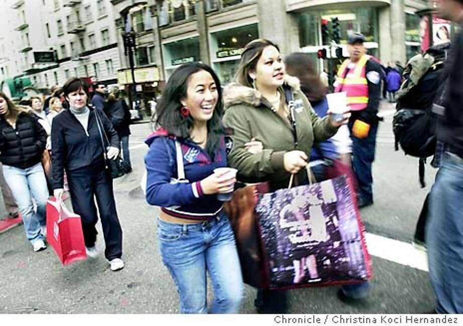 {shopping29b_112803_ckh}  Friends, (L to R) Janet Lee and Shawna McCarthy, both of SF, shop together, here on Powell, crossing Geary.After Thanksgiving shopping in U nion Square.  Photo by {CHRISTINA KOCI HERNANDEZ} / The San Francisco Chronicle Photo: CHRISTINA KOCI HERNANDEZ