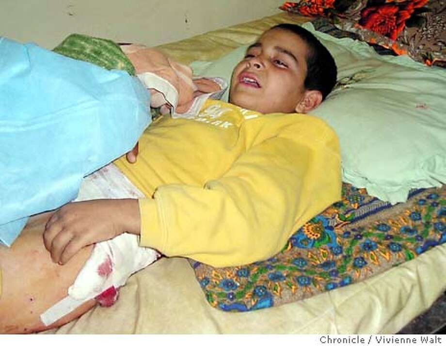 for Iraq02; Ali Al-Tashi, 9, lies weeping and injured in  Samarra's general hospital. His older brother says his  father was killed in Sunday's violence in the city,  but the boy does not yet know that. Photo by Vivienne Walt Samarra, Iraq Dec 1, 2003 Vivienne Walt, / Special To The Chronicle Photo: Vivienne Walt