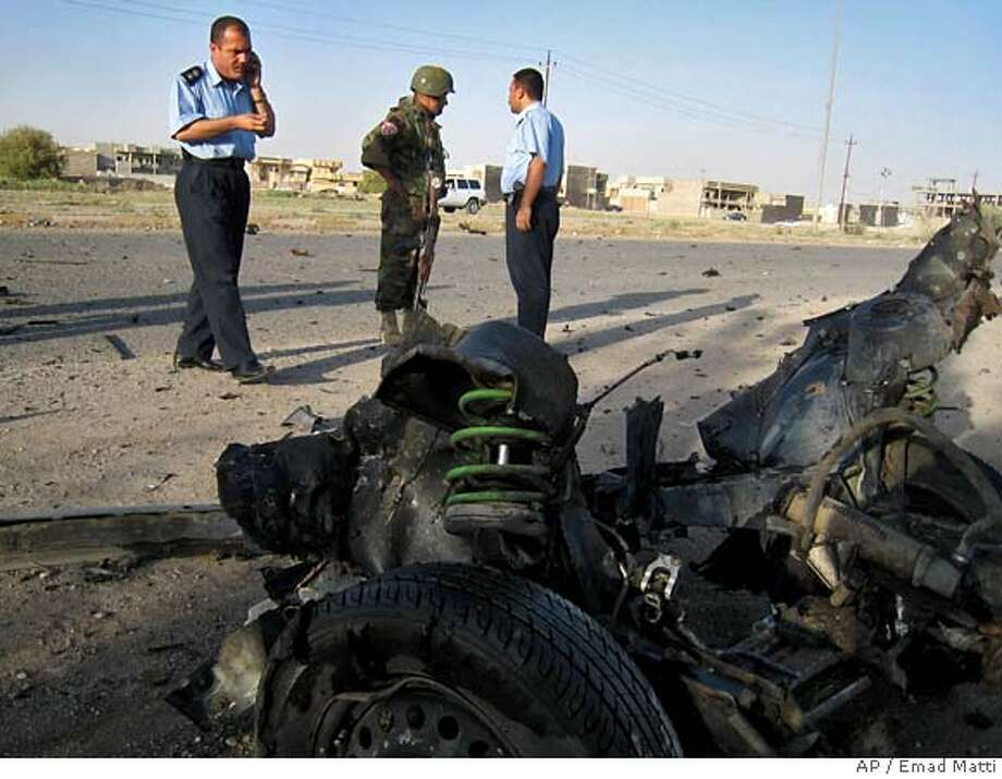 Iraqi policemen inspect the wreckage of a car used in a suicide bombing on a road in southern Kirkuk, 290 kilometers (180 miles) north of Baghdad, Iraq on Tuesday, Aug. 14, 2007. The attack, targeting a police patrol, killed one policeman and injured 13 policemen and two civilians, police said. (AP Photo/Emad Matti) Photo: EMAD MATTI