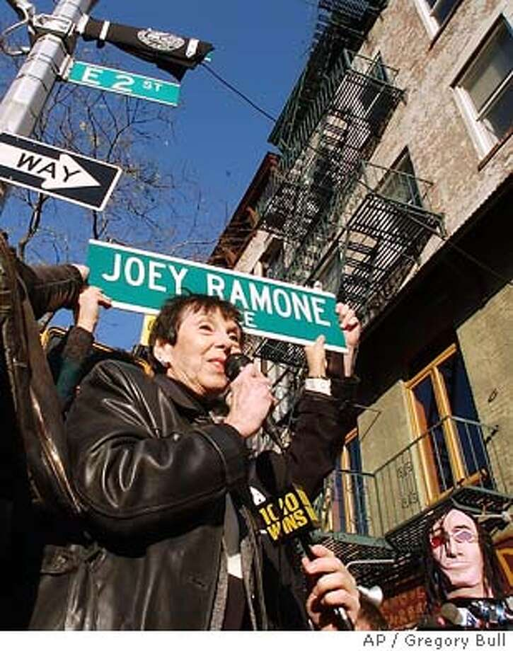 Charlotte Lesher, the mother of Ramones singer Joey Ramone, holds a sign that honors her son in New York Sunday, Nov. 30, 2003. The city of New York named the corner of Bowery and 2nd streets , in honor of the punk musician. (AP Photo/Gregory Bull) Photo: GREGORY BULL