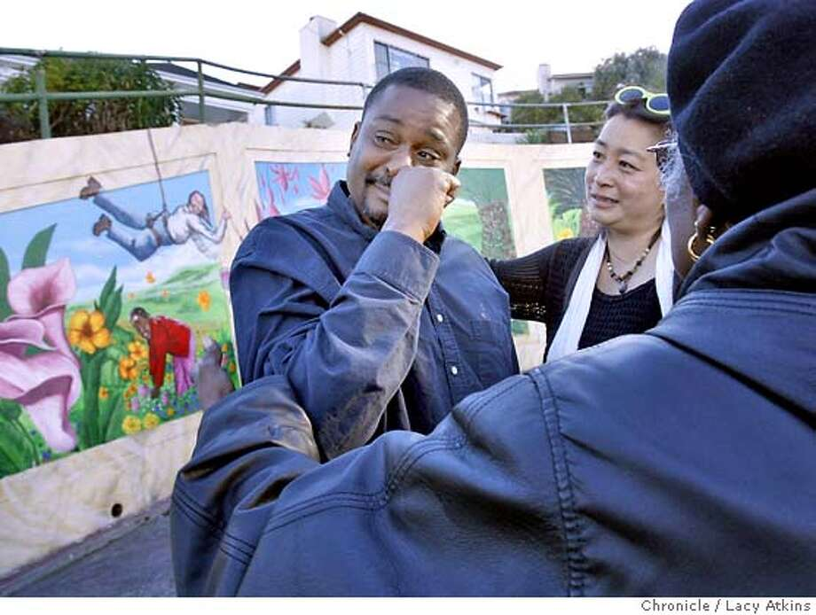 Rene Paige is comforted by Villy Wang and Corine Pettus as he begins to cry at the memorial for his father Karl Paige, Tuesday Aug. 14, 2007, in San Francisco, Ca. Karl was known as one of the people responsible for making cleaning up Quesada Street with murals and gardens. (Lacy Atkins /San Francisco Chronicle) Photo: Lacy Atkins