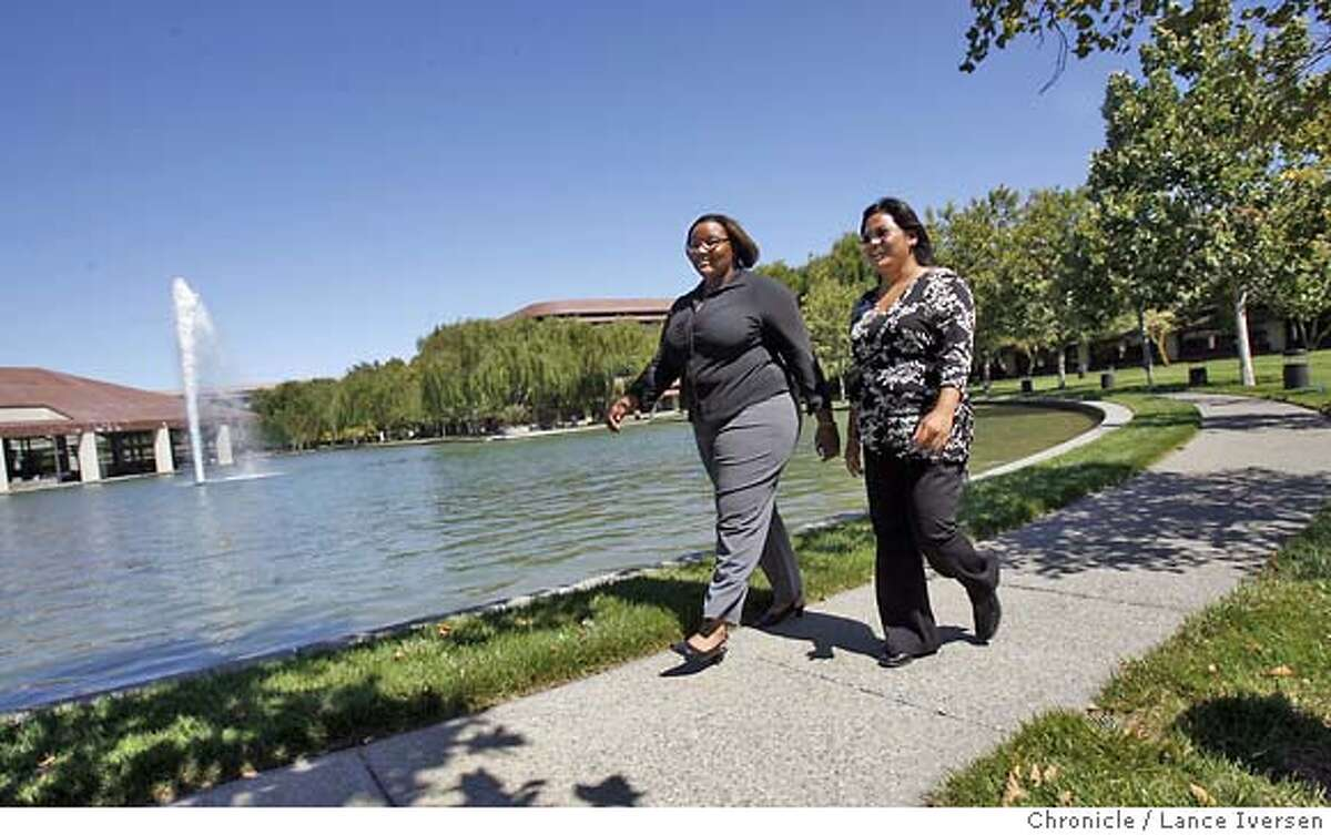 In this file photo, Chevron employees Dominique Ralph, (left) and Cecilia Yniquez walks around the company's suburban campus in San Ramon.