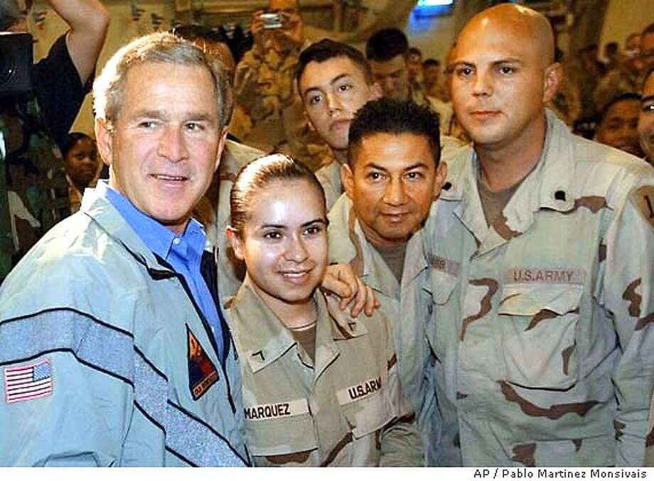 U.S. President George W. Bush stops to pose for photos with U.S. troops at Baghdad International Airport Thursday, Nov. 27, 2003, in Baghdad, Iraq, during a surprise Thanksgiving day visit. Bush boarded Air Force One unannounced from TSTC Airport in Waco, Texas, on Wednesday and made a brief stop at Andrews Air Force Base to switch planes before departing for Baghdad. (AP Photo/Pablo Martinez Monsivais) Photo: PABLO MARTINEZ MONSIVAIS