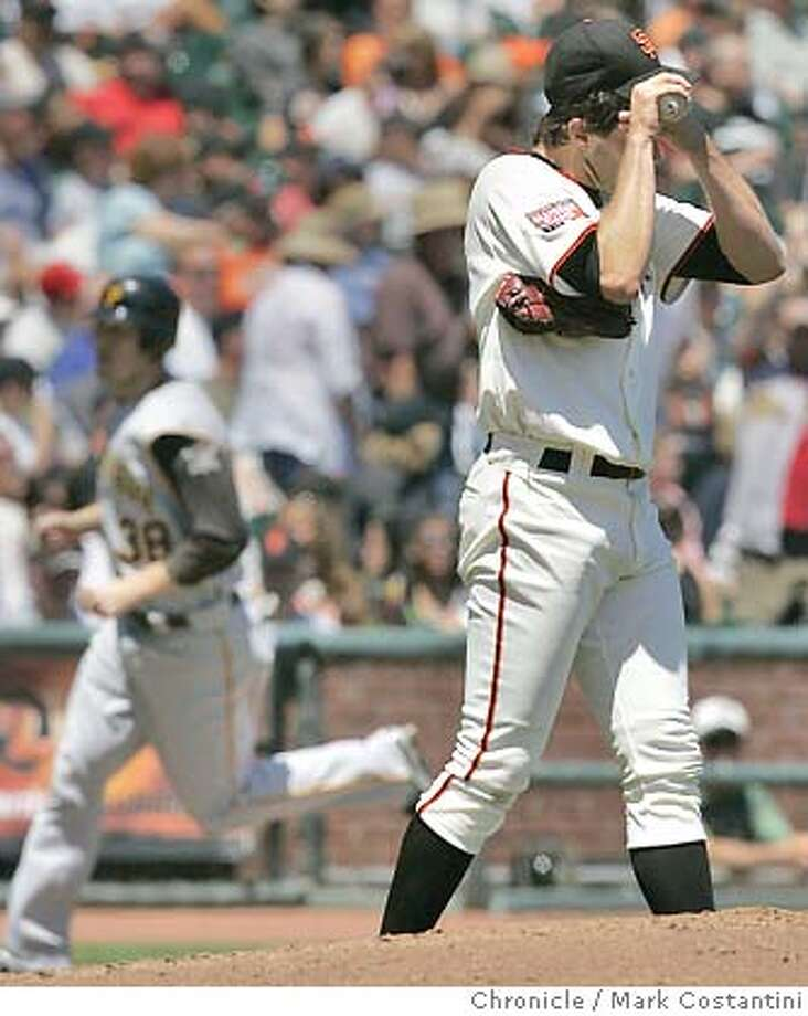 Giants pitcher Barry Zito holds his head after giving up a home run in the 6th inning to Pirates batter Josh Phelps, who circles the bases behind him.  Giants lose to the Pirates 5-0 at AT&T PArk Photo: Mark Costantini / S.F. Chronicle Photo: Mark Costantini