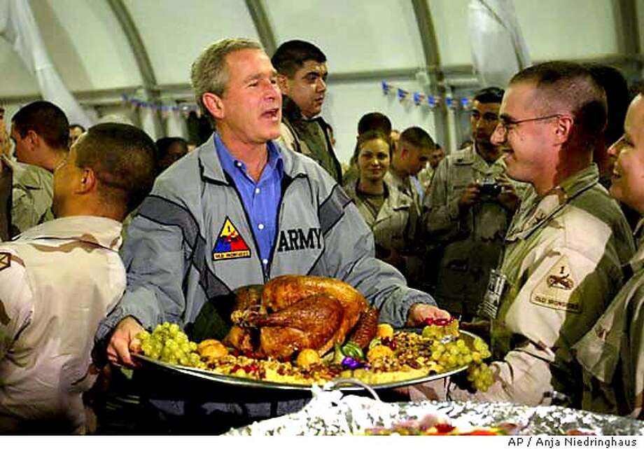 U.S. President George W. Bush carry a platter of turkey and fixings as he visits U.S. troops for Thanksgiving in Baghdad, Thursday, Nov 27, 2003. (AP Photo/Anja Niedringhaus, Pool) POOL Photo: ANJA NIEDRINGHAUS