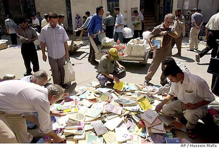 Iraqis buying used books at al-Motanabi street in Baghdad, Iraq, on Monday, July 8, 2002. Iraqis are compelled to resort to the old and used books because of the closure of the printing houses, partly due to the U.N. 12-year sanctions imposed on Iraq for its invasion of Kuwait in1990. (AP Photo /Hussein Malla) Iraqi residents buy used books, which were tightly controlled under Saddam Hussein, on al-Motanabi Street in Baghdad. Iraqi residents buy used books, which were tightly controlled under Saddam Hussein, on al-Motanabi Street in Baghdad. Photo: HUSSEIN MALLA
