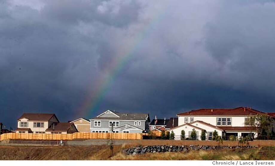 SACRAMENTO13_2851.JPG  A raibow falls on the Wisteria development at Twelve Bridges in Lincoln. People may be complaining that the Bay Area housing market is starting to cool off, but things are much worse in Sacramento. Home sellers, agents, builders and economists in the greater Sacramento area appears to be in particular trouble because the run-up in prices. DECEMBER 09, 2006  SACRAMENTO.  By Lance Iversen/San Francisco Chronicle Ran on: 12-17-2006  Sign twirlers Lindsay Lowry and Kallie Carmical, both 17, spin for the Whitney Ranch development in Lincoln during a rainstorm. MANDATORY CREDIT PHOTOG AND SAN FRANCISCO CHRONICLE/NO SALES MAGS OUT Photo: By Lance Iversen