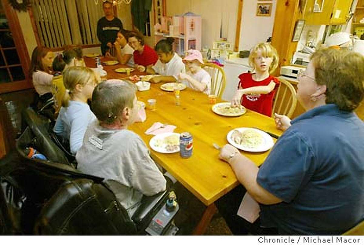 fleshandblood106_mac.jpg Susan Tom, right with her with her 9 children sit down to dinner. Susan Tom of Fairfield, has taken 9 disabled children into her home. Jonathan Karsh the former host of Evening Magazine, completed a documentary film on their lives . The film has received awards at the Sundance Film Festival as well as being included in the short list, (top 12 films) being considered as oscar contenders. 11/18/03 in Fairfield. MICHAEL MACOR/ The Chronicle Susan Tom puts her arm around 8-year-old Faith, who suffered severe burns when she was a baby.