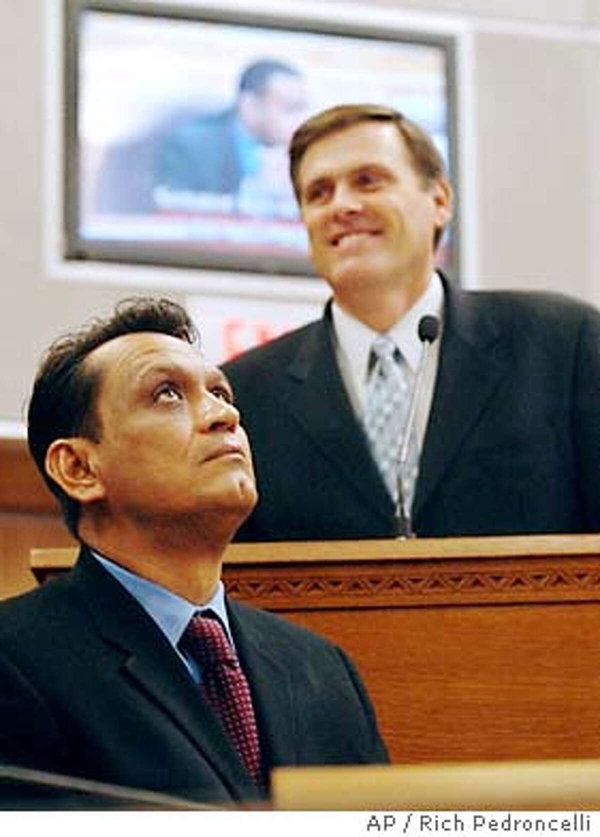 State Sen. Gil Cedillo, D-Los Angeles, left, author of the measure to give drivers licenses to undocumented immirgants, looks skyward while Sen. Rico Oller, R-San Andreas, author of a measure to repeal Cedillo's bill, smiles during a hearing of the Senate Transportation Committee at the Capitol in Sacramento, Calif., Monday, Nov. 24, 2003. Though Cedillo stood by his measure, which would have let 2 million undocumented immigrants obtain drivers' licenses, he urged his colleagues to repeal the law in the face of widespread public opposition. Oller's measure was approved by the committee and sent to the Senate floor. (AP Photo/Rich Pedroncelli