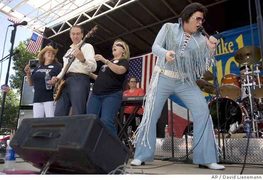 Presidential hopeful and former Arkansas Governor Mike Huckabee, second from left, plays with his band, Capital Offense as an Elvis Impersonator from Duncan Hunter's campaign helps out with a rendition of Johnny-Be-Good at the Iowa Straw Poll in Ames, Iowa, Saturday, Aug 11, 2007. (AP Photo/David Lienemann) Photo: David Lienemann