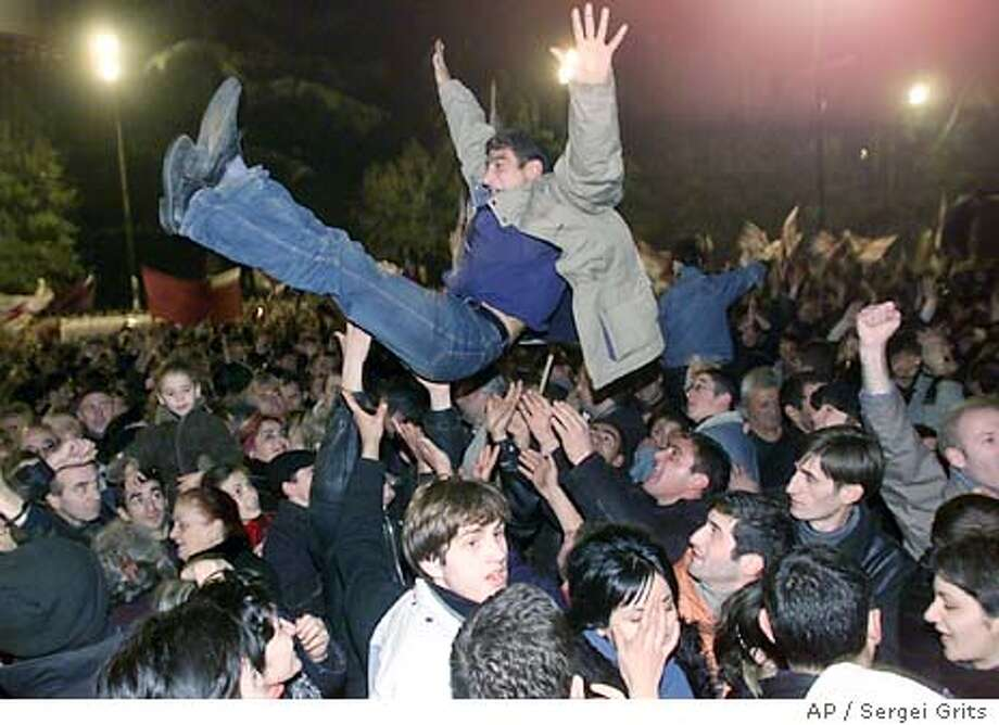 Opposition supporters celebrate Georgian President Eduard Shevardnadze's resignation in front of the Georgian Parliament in Tbilisi, Sunday, Nov. 23, 2003. Shevardnadze, under increasing pressure for weeks over fraud in parliamentary elections, announced his resignation on Georgian television on Sunday. (AP Photo /Sergei Grits) Photo: SERGEI GRITS