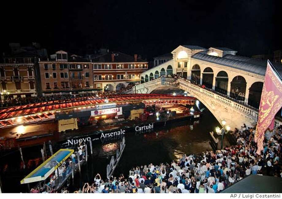 People gather on the canal bank to view the arched section of a new bridge, designed by Spanish-born architect Santiago Calatrava, as it is carried on a boat, near Rialto bridge, seen at right, in Venice, northern Italy, early Wednesday, Aug. 8, 2007. The new bridge on the Canal Grand will connect the train station to Piazzale Roma, a main car park, city officials said. It is not clear when it would open, but construction is expected to be completed around the end of the year. (AP Photo/Luigi Costantini) Photo: LUIGI COSTANTINI
