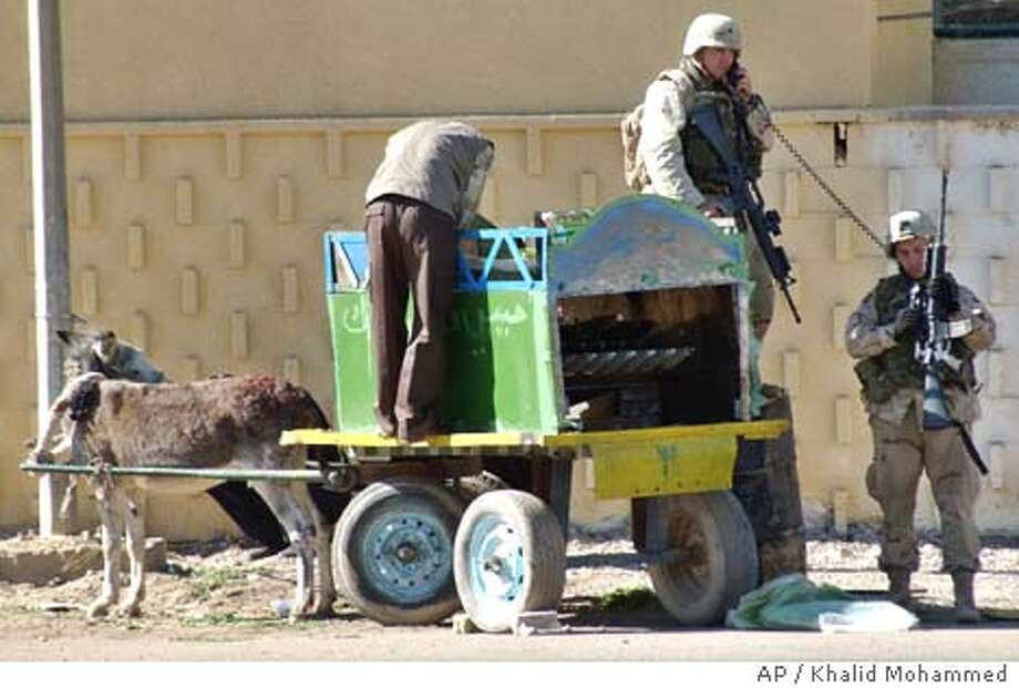 U.S. Army soldiers examine a rocket launcher mounted on donkey cart outside the Italian embassy in Baghdad, Friday, Nov. 21, 2003. More than a dozen rockets fired from donkey carts slammed into Iraq's Oil Ministry and two downtown hotels on Friday morning, brazen coordinated strikes at some of Baghdad's most heavily protected civilian sites that defied a U.S. crackdown. (AP Photo/Khalid Mohammed) Photo: KHALID MOHAMMED