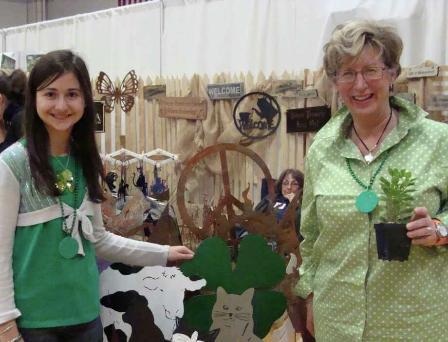 Angela Paraska, 11, and her neighbor Stefanie Baum, both of Fairfield, took a break from Baum's booth Bee Baum to shop Saturday at the Garden Expo. Both dressed in green for St. Patrick's Day and found a lucky shamrock among the metal garden scultpures at one of the 100 booths at the Fairfield event. Photo: Meg Barone / Fairfield Citizen freelance