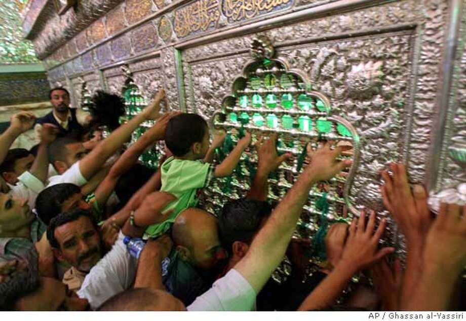 Shiite pilgrims touch the tomb of Imam Moussa al-Kadhim in the Kazimiyah neighborhood of north Baghdad, Iraq on Thursday, Aug. 9, 2007. Hundreds of thousands of Shiite pilgrims made their annual march to commemorate the eighth-century death of Imam Moussa al-Kadhim, a key Shiite saint. (AP Photo/Ghassan al-Yassiri) Photo: GHASSAN AL-YASSIRI