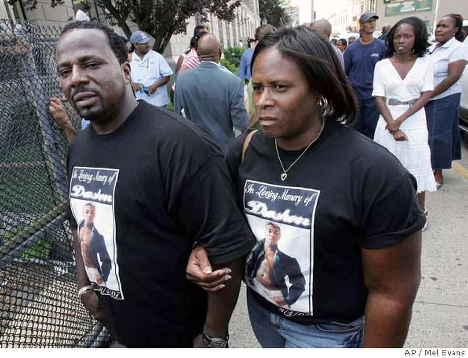 Dashon Harvey's father, James Harvey, left, and Mary Harris, wear Dashon's image on shirts as they stand outside Newark police headquarters, Thursday, Aug. 9, 2007, in Newark, N.J. Inside headquarters was Jose Carranza, who is wanted in connection with the killings of Dashon and two other college students who were lined up and fatally shot Saturday night. (AP Photo/Mel Evans) Photo: Mel Evans