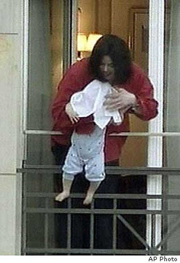 U.S. pop star Michael Jackson dangles an unidentified child, its head hidden by a towel, over a balcony of the Adlon Hotel in Berlin, Tuesday, Nov. 19, 2002, in this image made from television. Jackson, in Germany to attend an awards ceremony, had been waving to German fans, when he brought the baby onto the balcony. (AP Photo/APTN) ** GERMANY OUT: TELEVISION OUT **